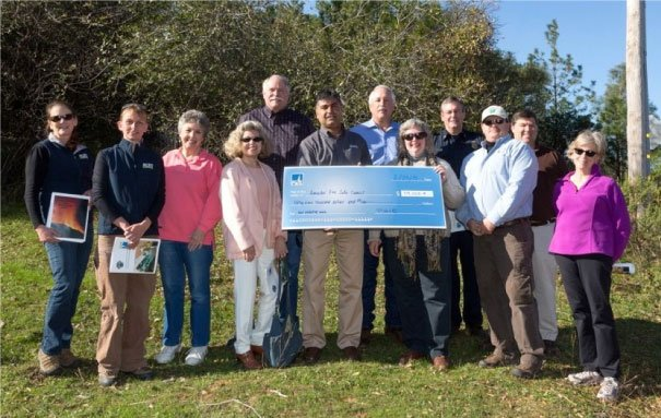 board members holding large check